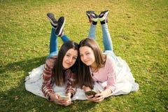 Dos muchachas escriben en teléfonos móviles Fotos de archivo libres de regalías