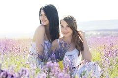 Dos muchachas están caminando en campo de la lavanda Fotografía de archivo