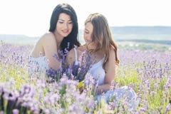 Dos muchachas están caminando en campo de la lavanda Imagenes de archivo