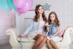 Dos muchachas están celebrando cumpleaños con la torta Imagenes de archivo