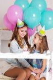 Dos muchachas están celebrando cumpleaños con la torta Imagen de archivo libre de regalías