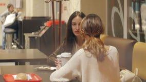 Dos muchachas están hablando en un café almacen de metraje de vídeo