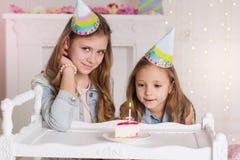 Dos muchachas están haciendo el deseo para el cumpleaños Foto de archivo libre de regalías