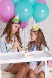 Dos muchachas están haciendo el deseo para el cumpleaños Fotografía de archivo