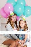Dos muchachas están haciendo el deseo para el cumpleaños con la vela Imagen de archivo libre de regalías