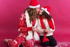 Dos muchachas están llevando la ropa del invierno en estudio Imágenes de archivo libres de regalías