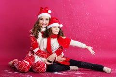 Dos muchachas están llevando la ropa del invierno en estudio Imagenes de archivo