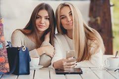Dos muchachas están mirando las fotos en smartphone fotografía de archivo libre de regalías