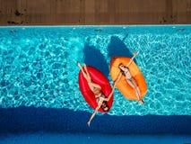 Dos muchachas están nadando en la piscina imagen de archivo
