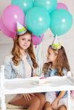 Dos muchachas están teniendo fiesta de cumpleaños en estudio Imagenes de archivo