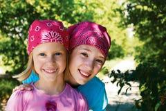 Dos muchachas felices al aire libre en pañuelos en sus cabezas Imagen de archivo libre de regalías