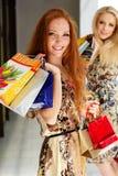 Dos muchachas felices atractivas hacia fuera que hacen compras Imagenes de archivo