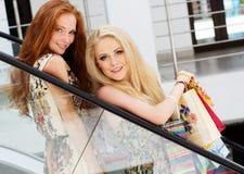 Dos muchachas felices atractivas hacia fuera que hacen compras Fotografía de archivo libre de regalías
