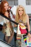 Dos muchachas felices atractivas hacia fuera que hacen compras Foto de archivo libre de regalías
