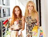Dos muchachas felices atractivas hacia fuera que hacen compras Imagen de archivo libre de regalías