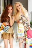 Dos muchachas felices atractivas hacia fuera que hacen compras Foto de archivo