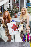 Dos muchachas felices atractivas hacia fuera que hacen compras Imágenes de archivo libres de regalías