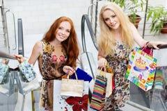 Dos muchachas felices atractivas hacia fuera que hacen compras Fotos de archivo libres de regalías