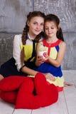 Dos muchachas felices con el pollo del bebé Imágenes de archivo libres de regalías