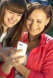 Dos muchachas felices con el teléfono móvil Fotos de archivo libres de regalías
