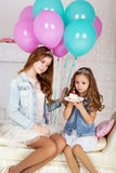Dos muchachas felices con la torta y los globos de cumpleaños Imagen de archivo libre de regalías
