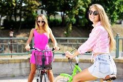 Dos muchachas felices con las bicicletas Fotos de archivo