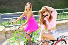 Dos muchachas felices con las bicicletas Imágenes de archivo libres de regalías