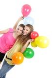 Dos muchachas felices con los globos coloridos Foto de archivo