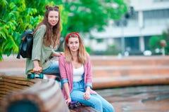 Dos muchachas felices con los monopatines al aire libre Mujeres deportivas activas que se divierten junto en parque del patín Imagenes de archivo