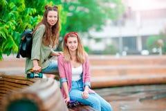 Dos muchachas felices con los monopatines al aire libre Mujeres deportivas activas que se divierten junto en parque del patín Fotos de archivo