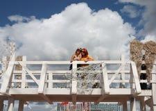 Dos muchachas felices en gafas de sol se colocan en el puente blanco Foto de archivo libre de regalías