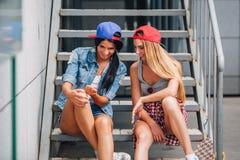 Dos muchachas felices que charlan en las escaleras Imagen de archivo