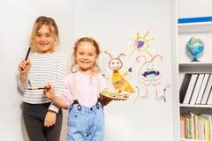 Dos muchachas felices que dibujan la imagen divertida en la pared Fotografía de archivo libre de regalías