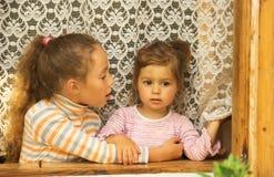 Dos muchachas felices que hablan en ventana en casa Fotografía de archivo