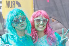 Dos muchachas felices que llevan los vidrios de sol cubiertos con el polvo del color Imagen de archivo