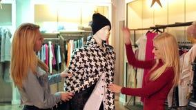 Dos muchachas felices que miran la ropa en un maniquí en una tienda de ropa Compras almacen de metraje de vídeo