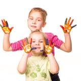 Dos muchachas felices que muestran las manos pintadas en colores brillantes Imagen de archivo libre de regalías