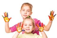 Dos muchachas felices que muestran las manos pintadas en colores brillantes Imagenes de archivo