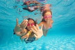 Dos muchachas felices que nadan debajo del agua clara de la piscina Imágenes de archivo libres de regalías