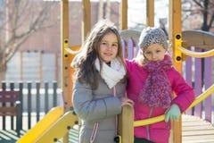 Dos muchachas felices que presentan en el patio Foto de archivo