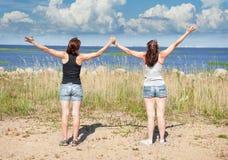 Dos muchachas felices que se colocan en la playa en verano imagen de archivo libre de regalías