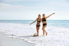 Dos muchachas felices que se divierten en la playa del mar fotografía de archivo