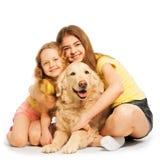 Dos muchachas felices que se sientan con su animal doméstico Fotografía de archivo libre de regalías