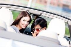 Dos muchachas felices que se sientan en el coche dan vuelta detrás Imagenes de archivo