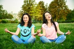Dos muchachas felices se sientan en la hierba Imágenes de archivo libres de regalías