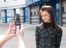 Dos muchachas felices toman cuadros en una calle Foto de archivo