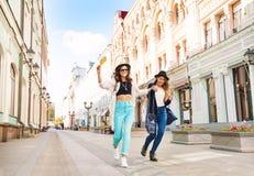 Dos muchachas feliz de salto mientras que camina Fotos de archivo libres de regalías