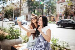 Dos muchachas finas apuestas con el pelo oscuro largo, vestido en pocilga casual, se sientan en el banco y toman un selfie, imagenes de archivo