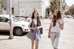 Dos muchachas finas lindas con el pelo largo, equipo casual que lleva, están caminando abajo de la calle en un día soleado imagen de archivo