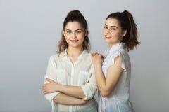 Dos muchachas gemelas de las hermanas hermosas en las blusas blancas Fotografía de archivo